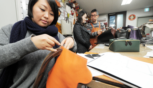 Blogger Kim Yu-ri demonstrates how to sew leather to make a laptop cover at atelier Chad Keane in Myeong-dong. (Ahn Hoon/The Korea Herald)