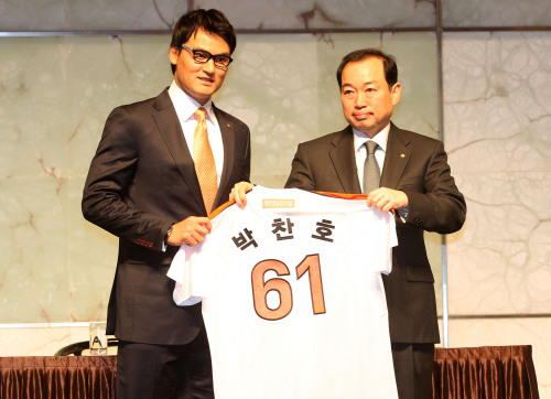 Hanwha Eagles CEO Jung Seung-jin (right) gives Park Chan-ho his jersey during the signing ceremony at the Plaza Hotel in Seoul on Tuesday.(Yonhap News)
