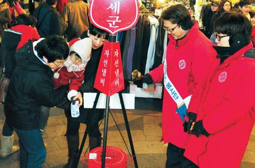 A family puts a bill into a Salvation Army red kettle in Myeongdong, Seoul, on Thursday. (Park Hyun-koo/The Korea Herald)