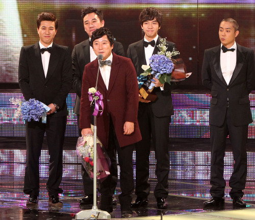 Comedian Lee Su-keun (center) makes an acceptance speech on behalf of the 'One Night, Two Days' team members who together received the grand prize at the KBS Entertainment Awards. (Yonhap News)