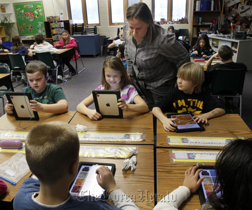 Julie Buckler, iPad teacher, instructs students using iPads in J.T. Kuzior's third grade class at Green Primary School in Green, Ohio, on Jan. 5. (Akron Beacon Journal/MCT)