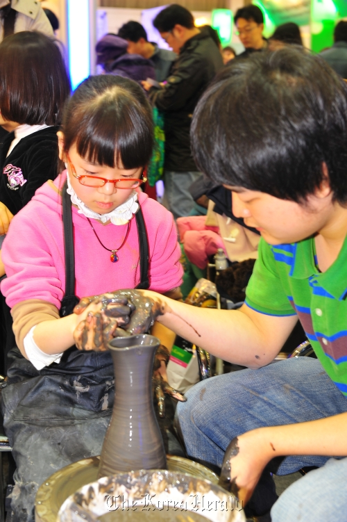 Children try their hand at pottery making during the 2011 Korea Travel Expo. (The Korea Tourism Association)