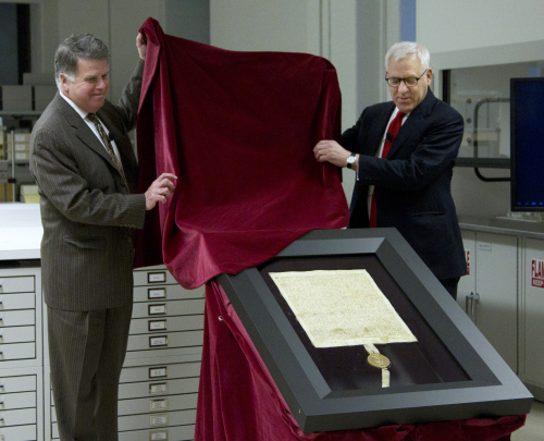 Carlyle Group co-founder and Magna Carta owner David Rubenstein (right) and Archivist of the U.S. David Ferriero, unveil the 1297 Magna Carta in its new state-of-the-art encasement at the National Archives in Washington, Thursday. (AP-Yonhap News)