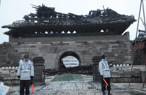 Police officers guard ruins of Namdaemun, a historic gate in Seoul that was severely damaged by arson in 2008. (Ahn Hoon/The Korea Herald)