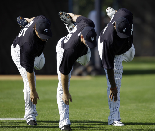 New York Yankees pitchers Phil Hughes (from left), Boone Logan and CC Sabathia stretch during spring training on Monday.(AP-Yonhap News)