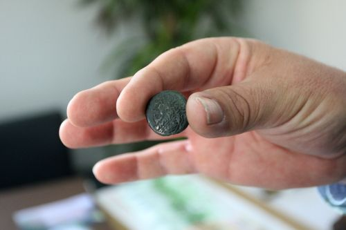 A police officer displays an ancient coin at the police station of Poligiros, 560km north of Athens on March 4, 2012. (AFP)