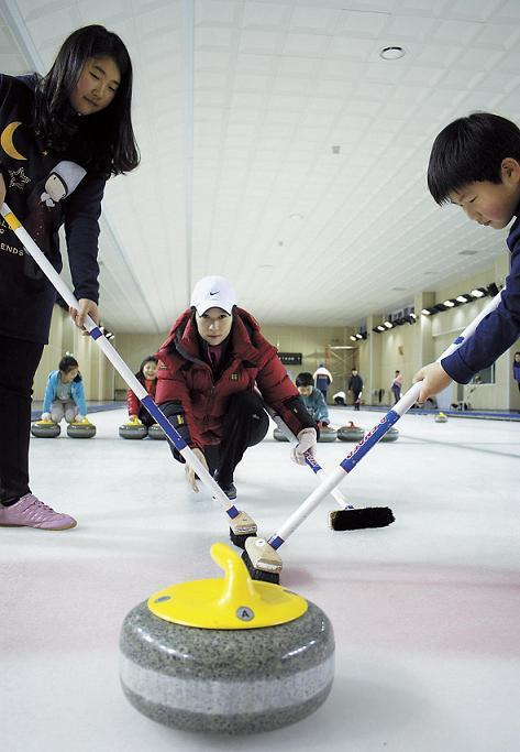 An instructor of Seoul Curling Club delivers the stone at the Taeneung Curling Rink on Sunday. (Oh Kyu-wook/The Korea Herald)