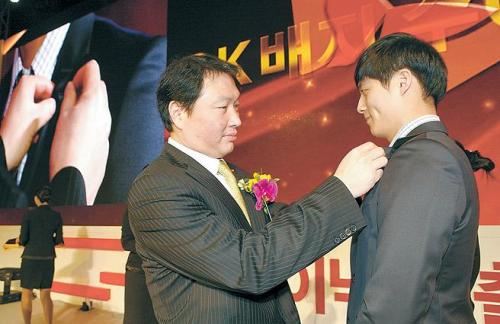 SK Group chairman Chey Tae-won (left) attaches an SK badge to a new Hynix employee during an inauguration event at the company's headquarters in Icheon, Gyeonggi Province, on Monday. (SK Hynix)