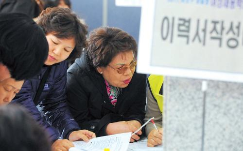 A middle-aged job-seeker writes her resume at a job fair in Seoul for women trying to reenter the workforce. (Lee Sang-sub/The Korea Herald)