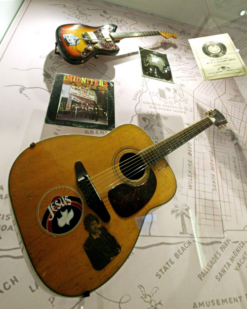 """This file photo shows a Harmony Sovereign acoustic guitar with a Jesus sticker among other items from Chicano musician Little Willie G at the exhibit, """"Trouble In Paradise: Music and Los Angeles, 1945-1975,"""" at the Grammy Museum in Los Angeles. (AP-Yonhap News)"""