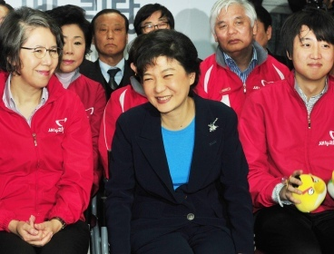 Saenuri Party chief Park Geun-hye (center) smiles while watching the election broadcast at the party's headquarters in Seoul on Wednesday. (Park Hyun-koo/The Korea Herald)