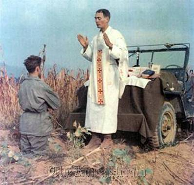 U.S. Army Chaplain Emil Kapaun (right) leads Mass at an impromptu altar set up on his jeep during the Korean War. (BBC News)