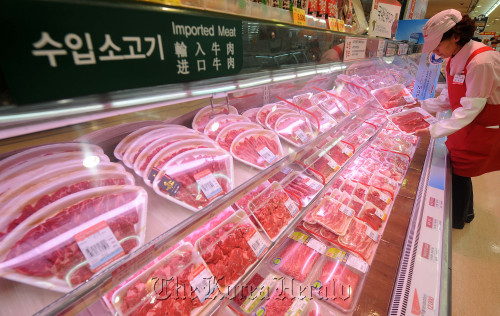 롯데마트 수입산소고기매장이상섭 기자. babtong@heraldcorp.com 2012.04.25A sales employee checks imported U.S. beef at a Lotte Mart in Seoul on Wednesday. Lee Sang-sub/The Korea Herald