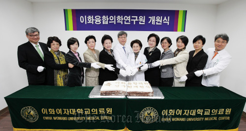 Ewha Womans University Medical Center head Suh Hyun-suk (seventh from left), Ewha Medical Collaboration Research Center chief Kim Seung-cheol (sixth from left) and others pose at the research center's opening ceremony on Monday in Seoul. (EWUMC)