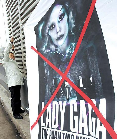 A civic group member hangs a banner showing a picture of U.S. pop star Lady Gaga on a wall to call for the cancellation of her concert, in Seoul,Monday. (AP-Yonhap News)