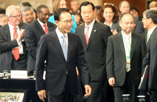 President Lee Myung-bak walks into the opening ceremony of the Green Growth Summit at the Lotte Hotel in downtown Seoul on Thursday. (Yonhap News)