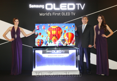 Kim Hyun-suk (Second from right), executive vice president of the visual display business at Samsung Electronics, introduces the firm's 55-inch OLED TV at a showcase in southern Seoul on Thursday. (Samsung Electronics)