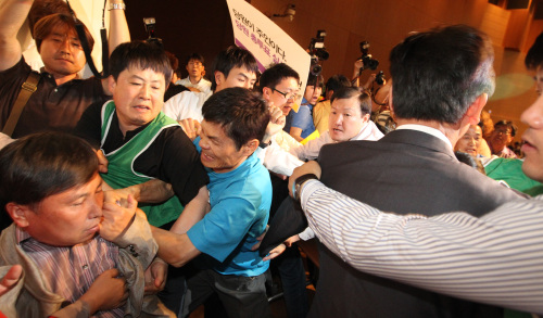 Cho Joon-ho (left), one of the four co-leaders of the Unified Progressive Party, is grabbed by the collar by a party member during the party's central committee meeting at a convention center in Ilsan, northwest of Seoul, on Saturday. (Yonhap News)