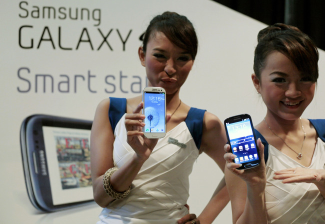 Models display a Samsung Galaxy S III, the latest smartphone in the company`s Galaxy lineups (AP-Yonhap News)