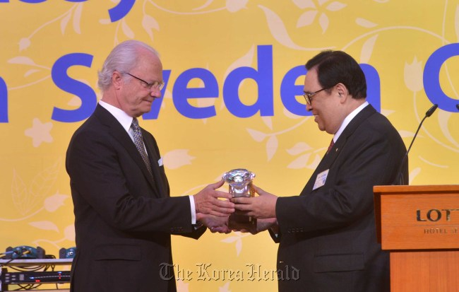 Lee Se-ung, president of the Korea Sweden Cultural Society, delivers a plaque of appreciation to Swedish King Carl XVI Gustaf during an event hosted by the association Wednesday.(Lee Sang-sub/The Korea Herald)