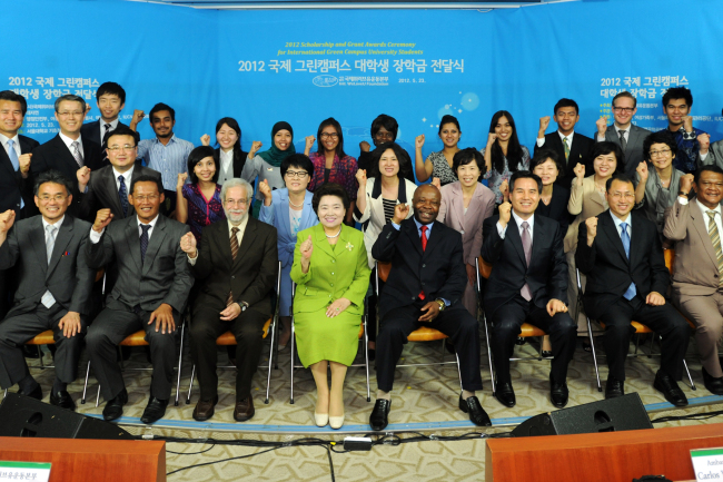 Zahng Gil-jah, Chairwoman of the Intl. WeLoveU Foundation, (4th from left, front row) and guests celebrate after the foundation awarded scholarships to university students from around the world to support their environmental protection activities in Seoul on May 23.