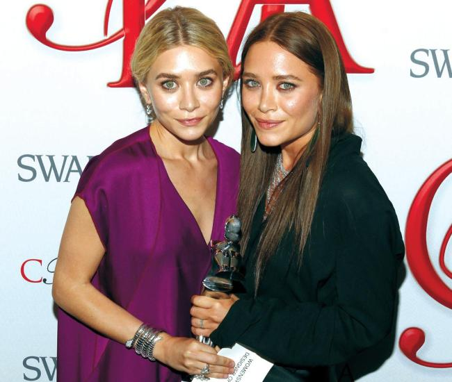Ashley Olsen (left) and Mary Kate Olsen, designers of The Row, pose backstage after winning Womenswear Designer of the Year at the CFDA Fashion Awards on Monday in New York. (AP-Yonhap News)