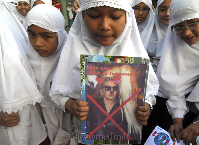 A Muslim elementary school student holds a defaced poster of U.S. pop singer Lady Gaga during a protest against her concert in Solo, Central Java, Indonesia. (AP-Yonhap News)
