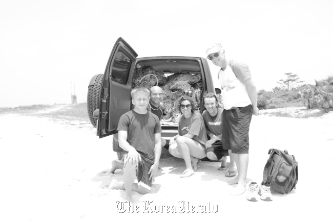 Volunteers gather to clean up a Jeju beach Saturday. (Sara Sokola)