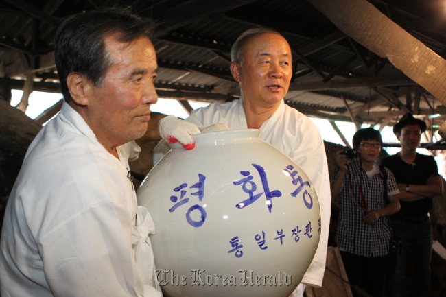 Minister of Unification Yu Woo-ik (right) and potter Kim Jeong-ok carry one of the six unification jars in Mungyeong, North Gyeongsang Province on Saturday. (Ministry of Unification)
