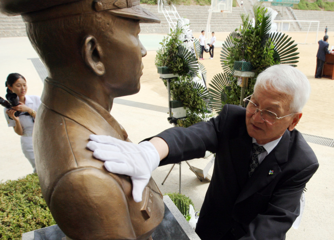 Yoon Du-ho, father of Lt. Cmdr. Yoon Young-ha, touches the bust of his son on Thursday at the Songdo High School in Incheon where he graduated. The officer is one of the six killed by a North Korean naval attack on June 29, 2002. (Yonhap News)