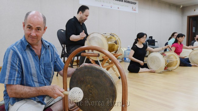 Grammy winner Henry Kaiser plays a jing, a traditional Korean percussion instrument, at the National Gugak Center in Seoul, Friday. (Chung Hee-cho/The Korea Herald)