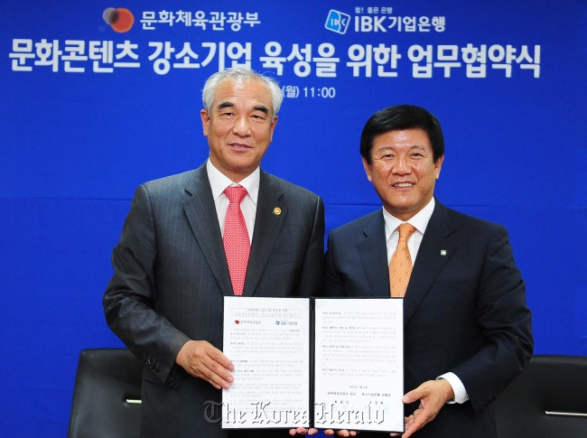 Culture Minister Choe Kwang-shik (left) and IBK president & CEO Cho Jun-hee pose for photo after signing an memorandum of understanding for supporting local content developers with 138 billion won worth fund at the Culture Ministry in Seoul, Monday. (Culture Ministry)