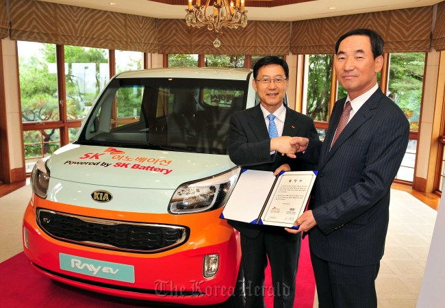 Kia Motors CEO Lee Sam-woong (right) and SK Innovation CEO Koo Ja-young pose after signing a memorandum of understanding at a Seoul hotel on Wednesday. (Kia Motors)