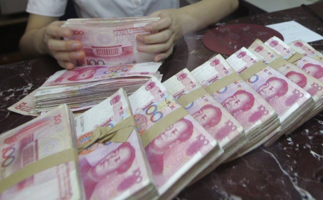 An employee counts 100 yuan banknotes at a branch of Bank of Communications in Shenyang, China. (Bloomberg)