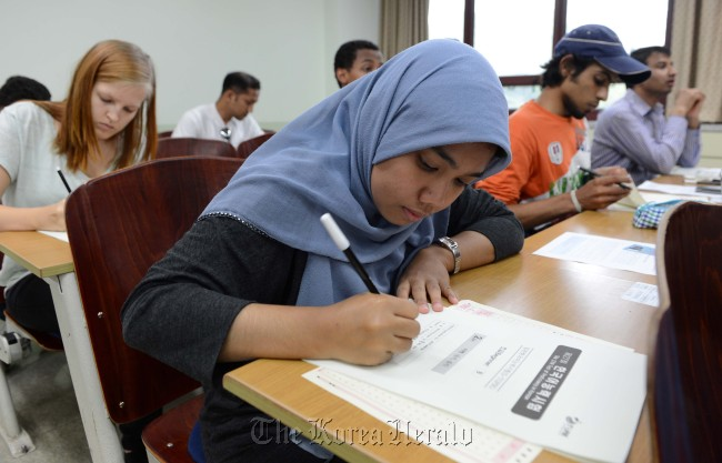 Foreign students take TOPIK (Test of Proficiency in Korean) at Kyung Hee University in Seoul on Sunday. A record number of students ― 19,344 of them ― took the test on Sunday at 14 locations nationwide. (Park Hae-mook/The Korea Herald)
