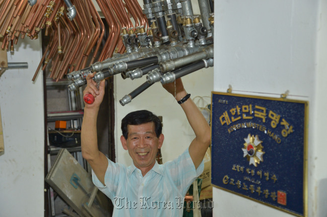 Lee Young-soo grabs a boiler pipe. (Kim Myung-sub/The Korea Herald)