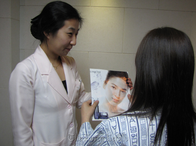 Clutching a picture of her favorite Korean actress, whom she aims to resemble, a patient prepares for nose surgery at a plastic surgery clinic in Seoul. ( MCT)