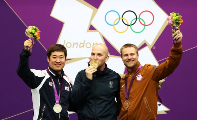 Gold medalist Niccolo Campriani (center) of Italy, silver medalist Kim Jong-hyun (left) of South Korea and bronze medalist Matthew Emmons of the United States pose at awarding ceremony of men's 50m rifle 3 positions of shooting at London 2012 Olympic Games, London, Britain, Aug. 6, 2012. (Xinhua-Yonhap News)
