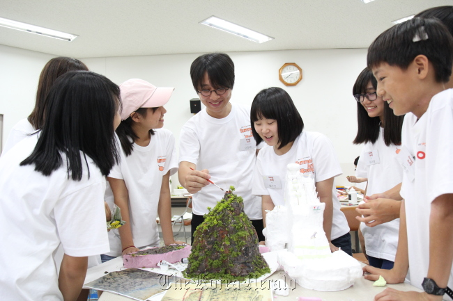Sculptor Lee Wan (center) gives advice to junior artists participating in the annual art camp supported by K-Auction and Mecenat Council on Wednesday at a training center in Seoul. ( Mecenat Council)