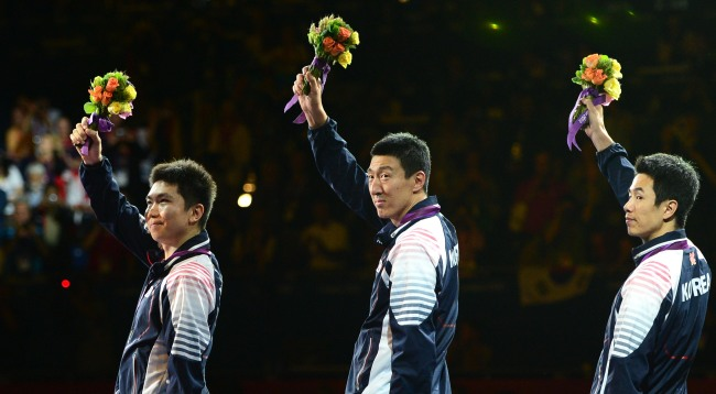 Korean table tennis team members Ryu Seung-min (from left), Oh Sang-eun and Joo Sae-hyuk salute the crowd after winning silver medals on Wednesday. (London Olympic Joint Press Corps)