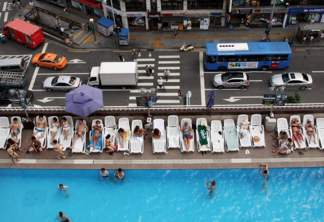 People enjoy the sun and the water at Hamilton Hotel's rooftop swimming pool in Itaewon, Seoul. (Yonhap News)