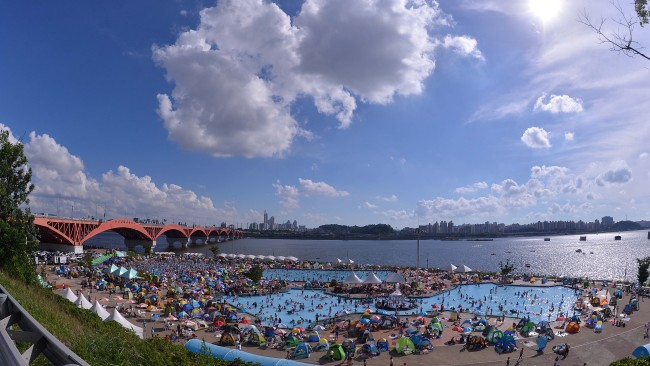 Mangwon Hangang Park's swimming pool, one of the several outdoor pools along the Han River operated by the city, is packed with Seoulites trying to escape the heat. (Lee Sang-sub/The Korea Herald)