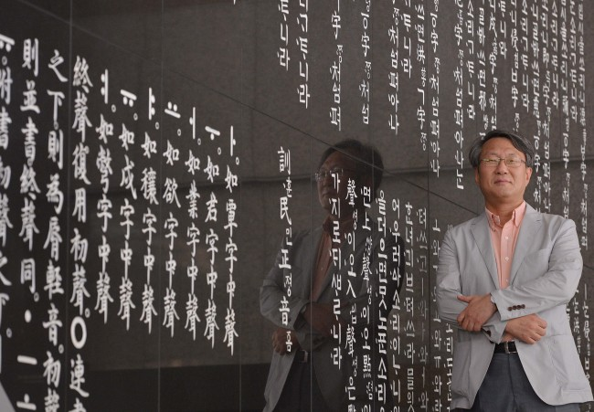 Song Hyang-keun, president of the International Korean Language Foundation, stands beside the wall engraved with texts in Huminjeongeum at the National Institute of the Korean Language in Banghwa-dong, Seoul, Monday. (Lee Sang-sub/The Korea Herald)