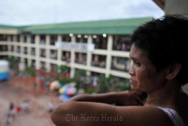 A flood affected resident looks from a window of a school building serving as an evacuation center in Marikina town, suburban Manila on Aug. 9. (AFP-Yonhap News)