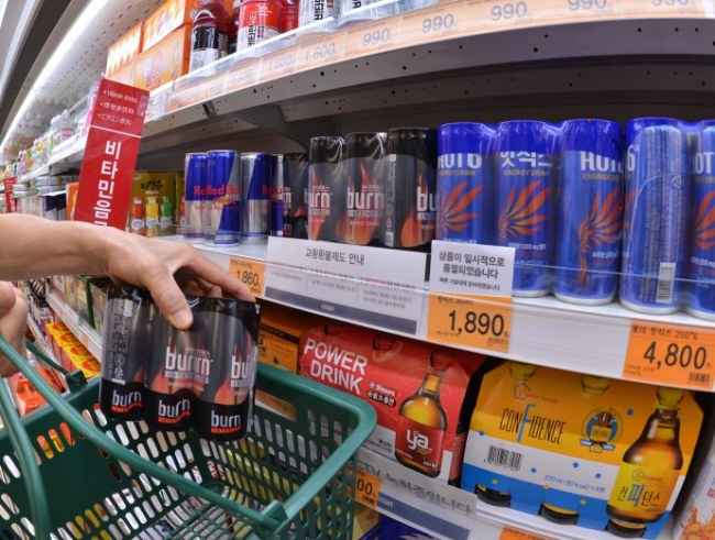 A consumer buys an energy drink at a supermarket in Seoul on Thursdday. (Lee Sang-sub/The Kore Herald)