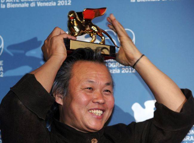 Director Kim Ki-Duk holds the Golden Lion for best movie on his head during a photocall following the award ceremony of the 69th Venice Film Festival on Saturday at Venice Lido. (AFP-Yonhap News)
