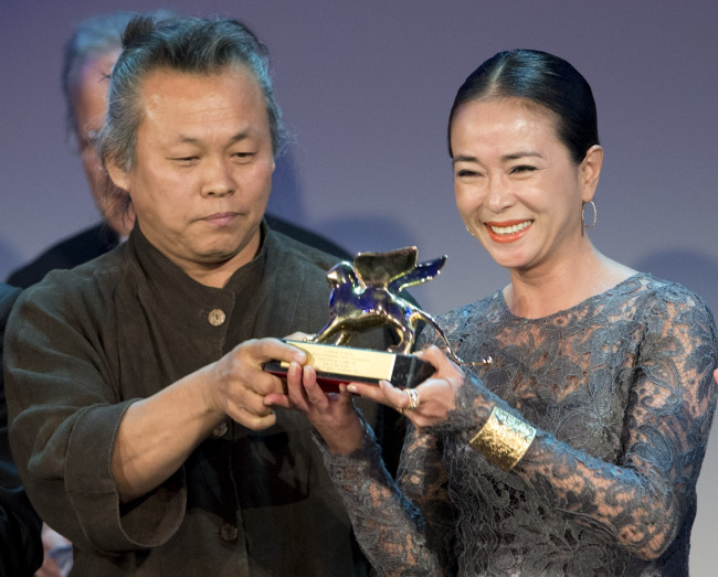 """Director Kim Ki-duk (left) and actress Cho Min-soo show their Golden Lion for best movie for the film """"Pieta"""" at the 69th edition of the Venice Film Festival in Venice, Italy, Saturday. (AP-Yonhap News)"""