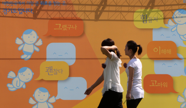 Participants walk in front of a panel written on with words of consolation during an event held at the Gyeonggi Provincial Government office to promote suicide prevention on Friday. (Yonhap News)