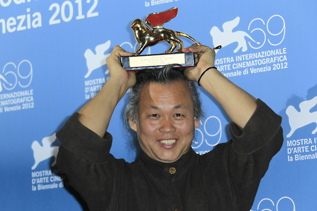 """Kim Ki-duk shows the Golden Lion he won for his movie """"Pieta"""" at the awards photo call during the 69th edition of the Venice Film Festival in Venice, Italy, Saturday. (AP-Yonhap News)"""