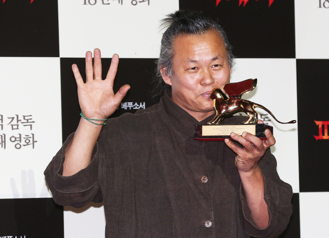 Kim Ki-duk holds his Venice Film Festival Golden Lion Award at a Press Conference at Megabox in Dongdaemun in Seoul earlier this month. (Yonhap News)
